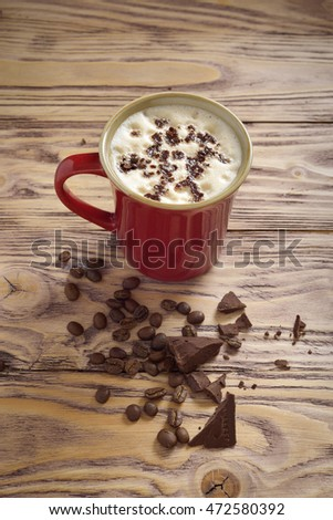 coffee in a red mug on a wooden table and coffee beans