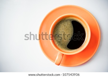 Coffee in an orange cup - stock photo