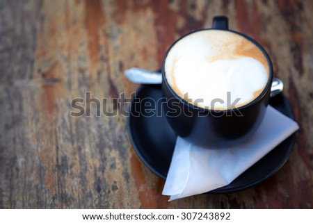Coffee in black cup on wood table - stock photo