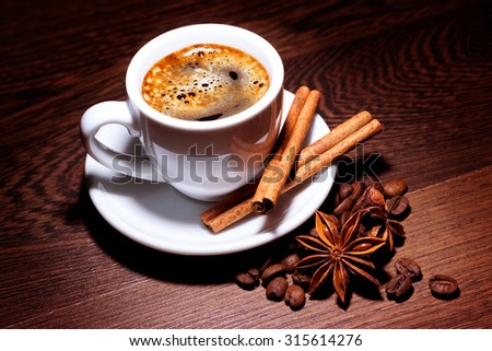 coffee in cup with milk, cinnamon and anise stars on wooden surface - stock photo