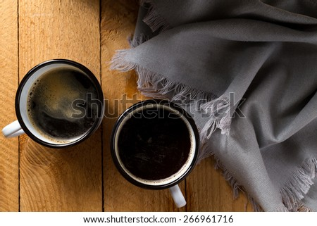 Coffee in enamel mug on a wooden table with a gray napkin (top view) - stock photo