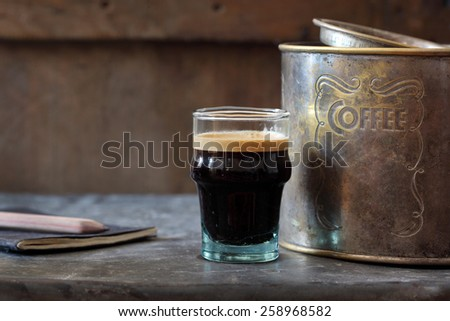 coffee in glass cup on table with rusted tin box and notebook and pencil - stock photo