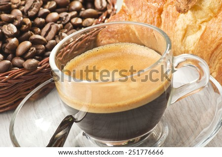 coffee in glass cup with croissants and coffee beans - stock photo