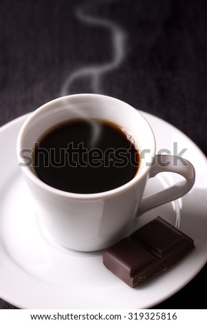 Coffee in white ceramic cup with chocolate on dark background - stock photo