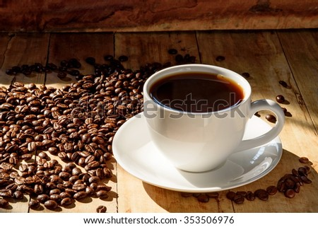coffee in white cup and coffee beans on older wood background with ligh from windows - stock photo