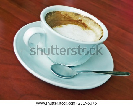 Coffee in white cup with a spoon in plate and mahogany table as background - stock photo