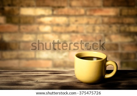 Coffee in yellow cup on wooden table opposite a defocused brick wall for background. Collage. Selective Focus. Toned. - stock photo