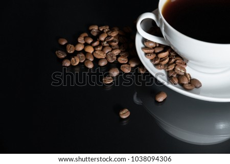 coffee is poured into a white cup with roasted coffee beans scattered on a black surface table