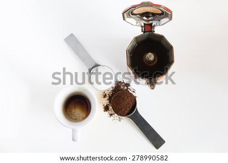 Coffee, italian way with spoons, cup, sugar, coffee powder and moka - stock photo
