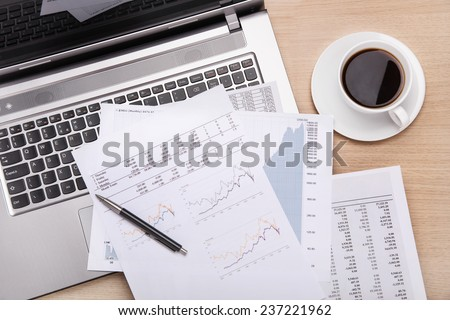 Coffee,laptop and paperwork on office desk - stock photo
