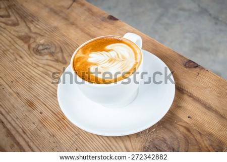 Coffee latte art on wood table - stock photo