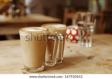 coffee latte in two tall glasses and sugar bowl, shallow dof - stock photo