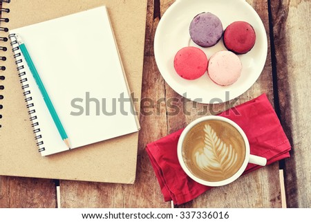 Coffee latty notepad and french macarons on the wooden background. vintage effect - stock photo