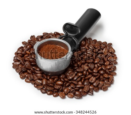Coffee machine filter holder with ground coffee on coffee beans heap isolated on white - stock photo