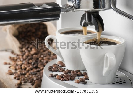 coffee machine makes two coffee with coffee beans on background - stock photo