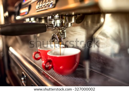 coffee machine preparing fresh coffee and pouring into red cups at restaurant, bar or pub. - stock photo