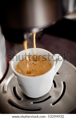 Coffee maker pouring hot espresso coffee in a cup