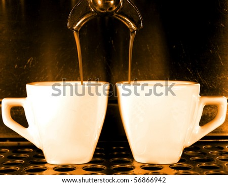 Coffee maker pouring hot espresso coffee in two cups - stock photo