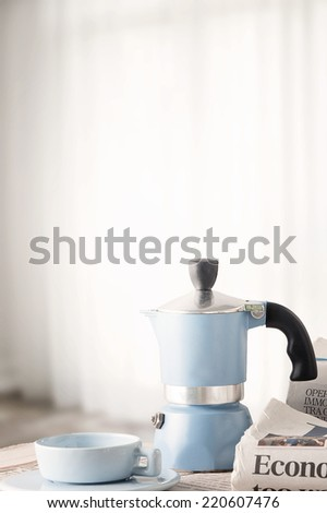 Coffee maker with cup of coffee and newspapers