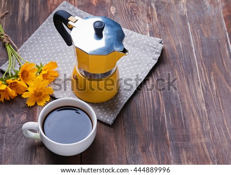 Coffee maker, yellow flowers and cup with coffee on wooden table.