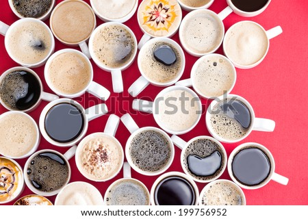 Coffee mecca with multiple assorted types and flavors of coffee in identical white mugs artistically arranged with converging handles in the center on a red background, overhead view - stock photo