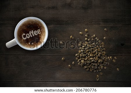 Coffee mug and beans on old wooden table - stock photo