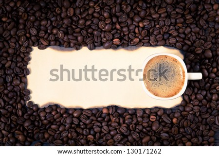 Coffee mug on a sheet of old paper on the background of coffee beans.
