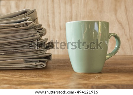 Coffee mug on a wooden table with a stack of newspapers