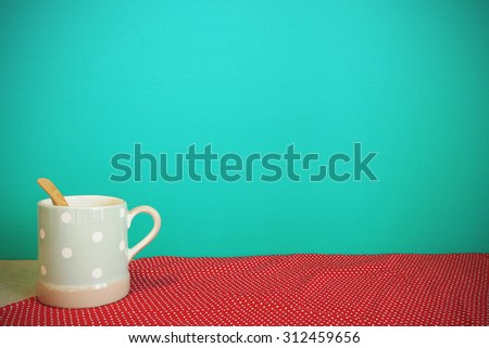 Coffee mug on tablecloth front mint green background. Vintage effect. - stock photo