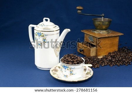 coffee mug on the table with a blue tablecloth, poured out coffee beans - stock photo