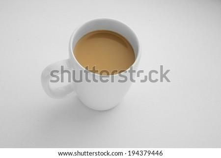 coffee mug with cappuccino on light grey background. Mimimalistic studio shoot. Top view - stock photo