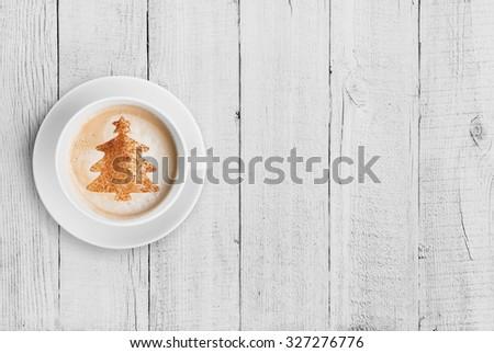 coffee mug with christmas tree shape on white wood table - stock photo