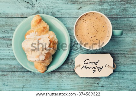 Coffee mug with croissant and notes good morning on turquoise rustic table from above, cozy and tasty breakfast, vintage toned - stock photo
