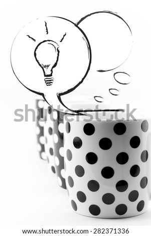 Coffee mugs with speech bubbles and light bulb isolated on white - stock photo