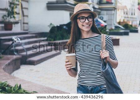 Coffee on the go.  Beautiful young woman holding coffee cup and smiling while walking along the street - stock photo