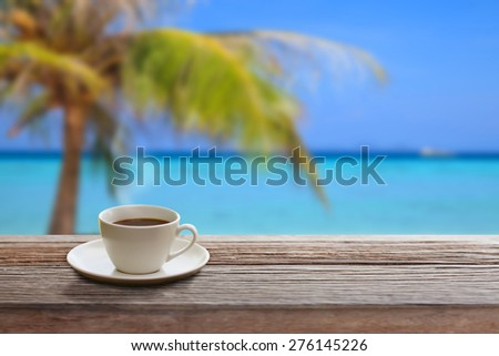 Coffee on wood table in the beach. - stock photo