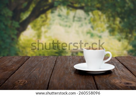 Coffee on wooden table with beautiful autumn forrest background - stock photo