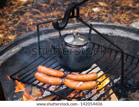 Coffee pan and sausages over the campfire with fire and flames - stock photo