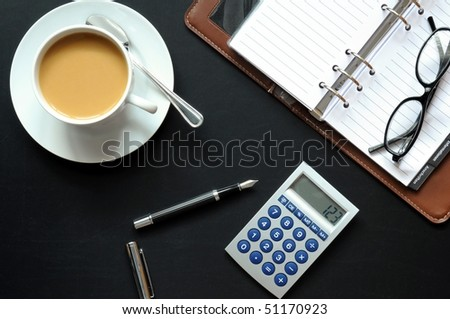 coffee pen phone and paper on desk in office