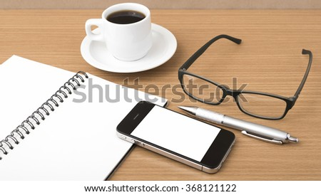 coffee,phone,notepad and eyeglasses on wood table background