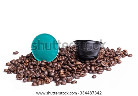Coffee pods and beans isolated over white background - stock photo
