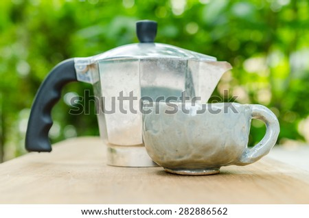 coffee pot on wooden board with blur background
