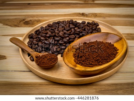 Coffee powder and Coffee beans on wooden plates at wooden background. Vintage Filter - stock photo