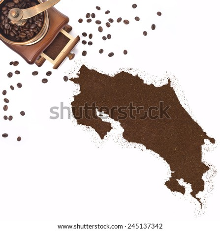 Coffee powder in the shape of Costa Rica and a decorative coffee mill.(series) - stock photo