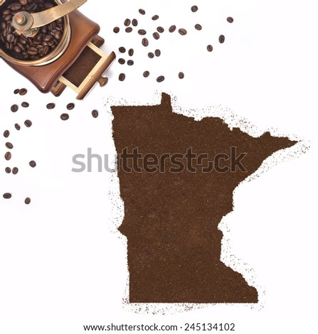 Coffee powder in the shape of Minnesota and a decorative coffee mill.(series) - stock photo