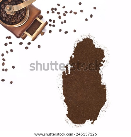Coffee powder in the shape of Qatar and a decorative coffee mill.(series) - stock photo