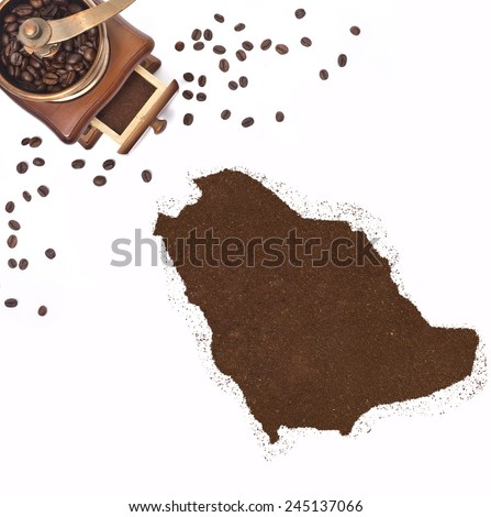 Coffee powder in the shape of Saudi Arabia and a decorative coffee mill.(series) - stock photo