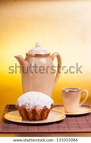 Coffee service and muffin on a plate