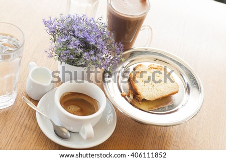 Coffee shop table settings, coffee cup, purple  flower and dessert  - stock photo