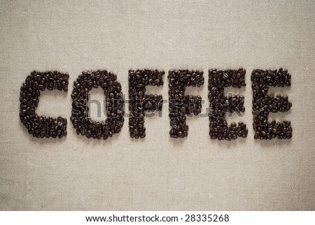 Coffee spelled with Coffee beans on a sack background. - stock photo